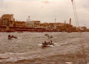 סירות מלוות את הספינה ברקע נמל פורט סעיד.