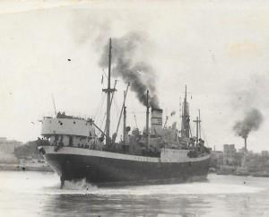 """האניה 'קוממיות' נכנסת לנמל מונופולי די ברי' בהפלגת סיום.  מגורי הגדנ""""עים במבנה מעל ירכתי האנייה."""